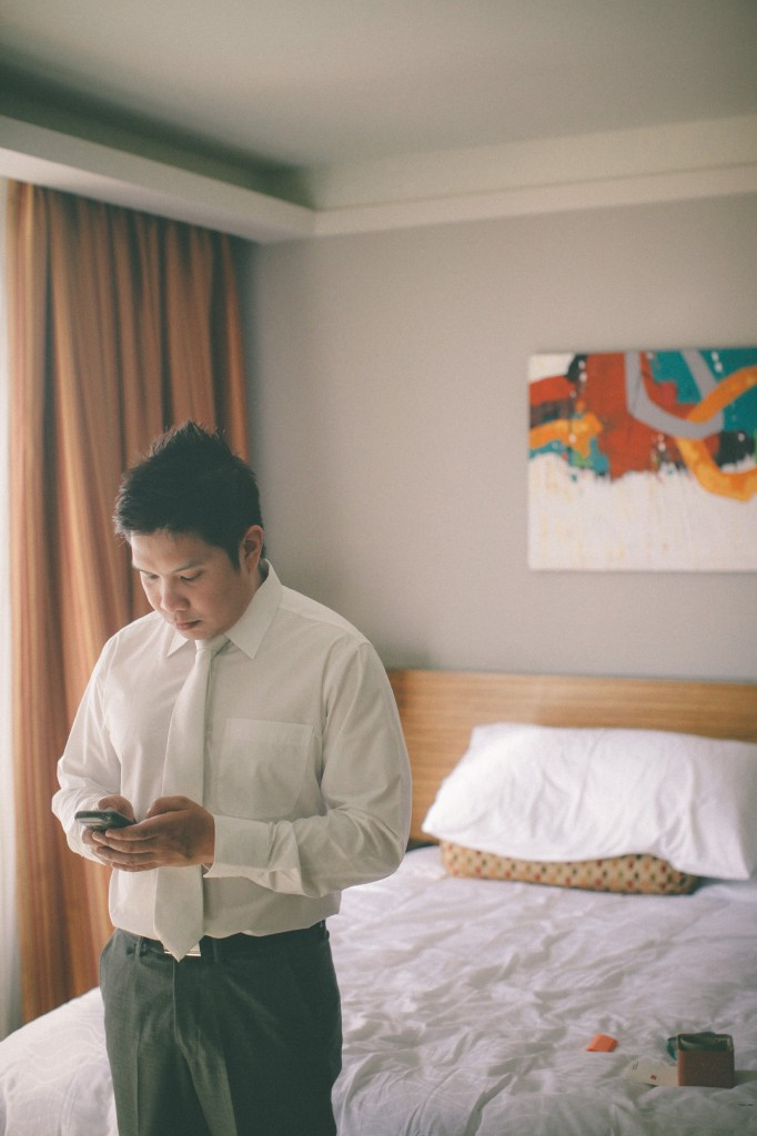 san   diego wedding photographer | man in white shirt texting in front of bed