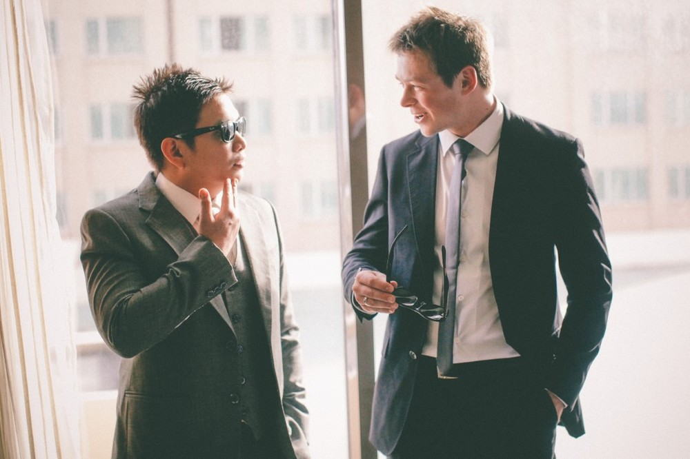 san   diego wedding photographer | man in dark blue suit talking to man in shades   and suit