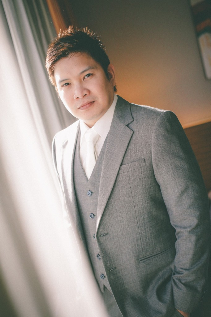 san   diego wedding photographer | man with grey suit standing in front of slightly   open curtains