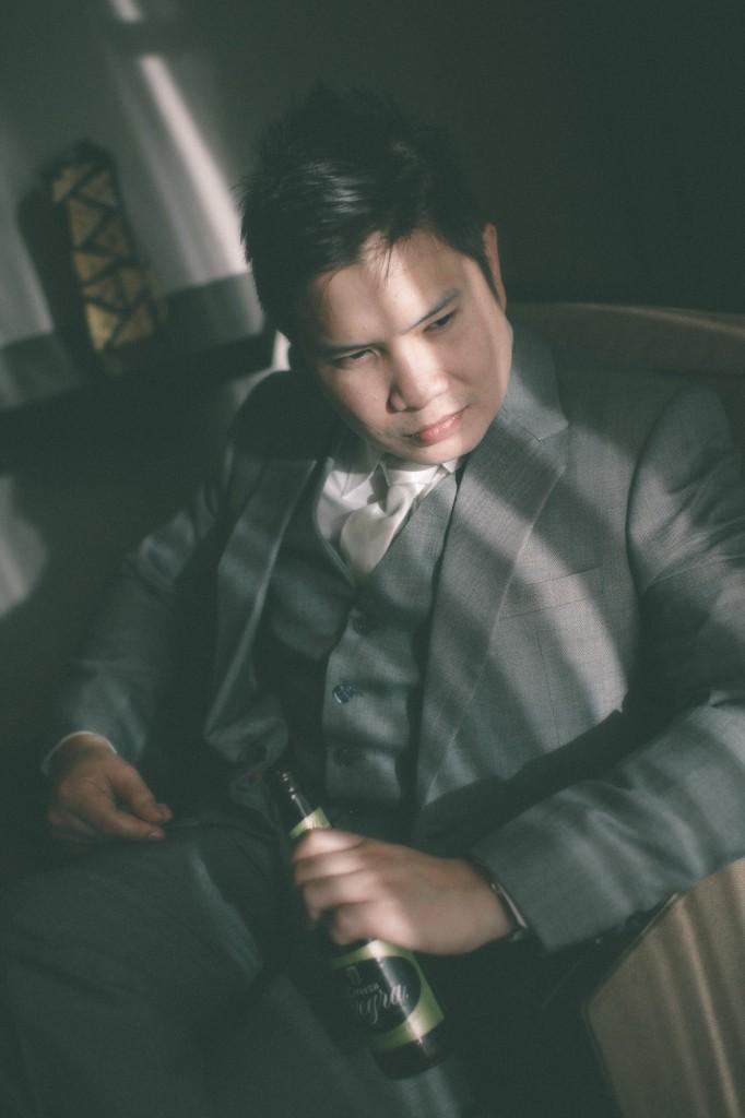 san   diego wedding photographer | man in grey suit sitting down holding beer   bottle