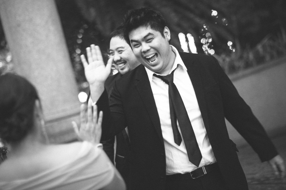 san   diego wedding photographer | man in black and white suit laughing with hand   up