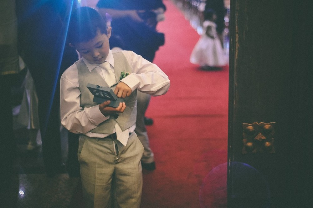 san   diego wedding photographer | child in grey suit playing with box
