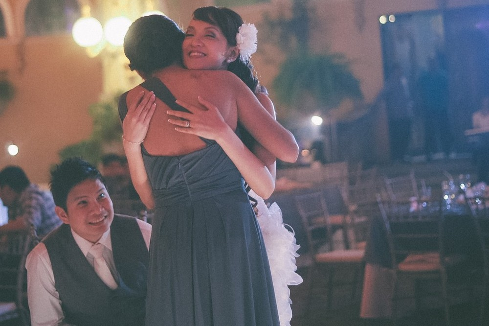 san   diego wedding photographer | bride hugging woman in blue dress with groom   behind them