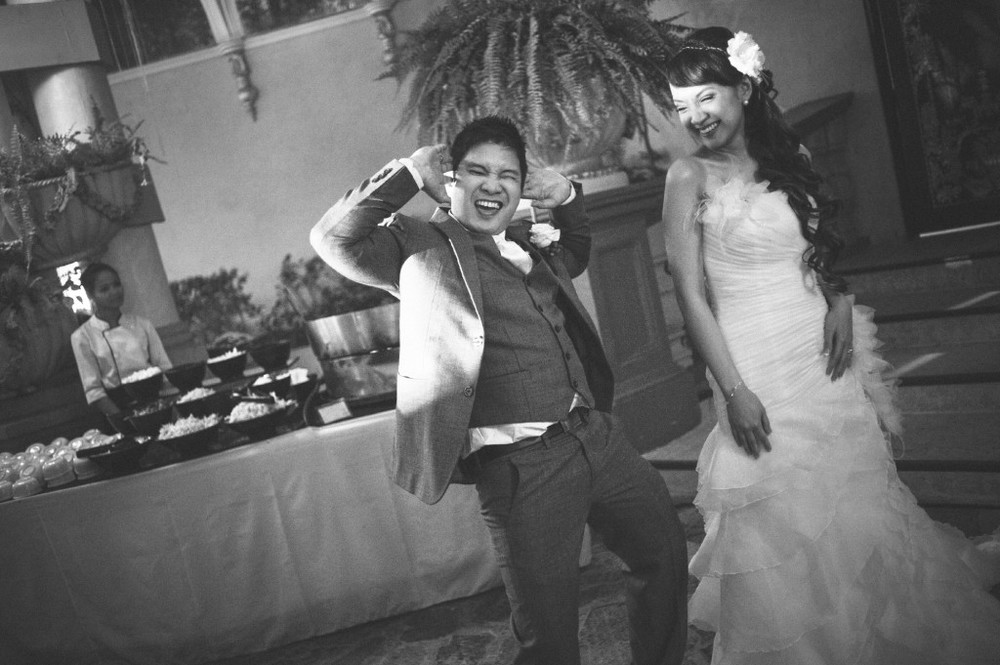 san   diego wedding photographer | monotone shot of bride and groom dancing   laughing with table of food behind them