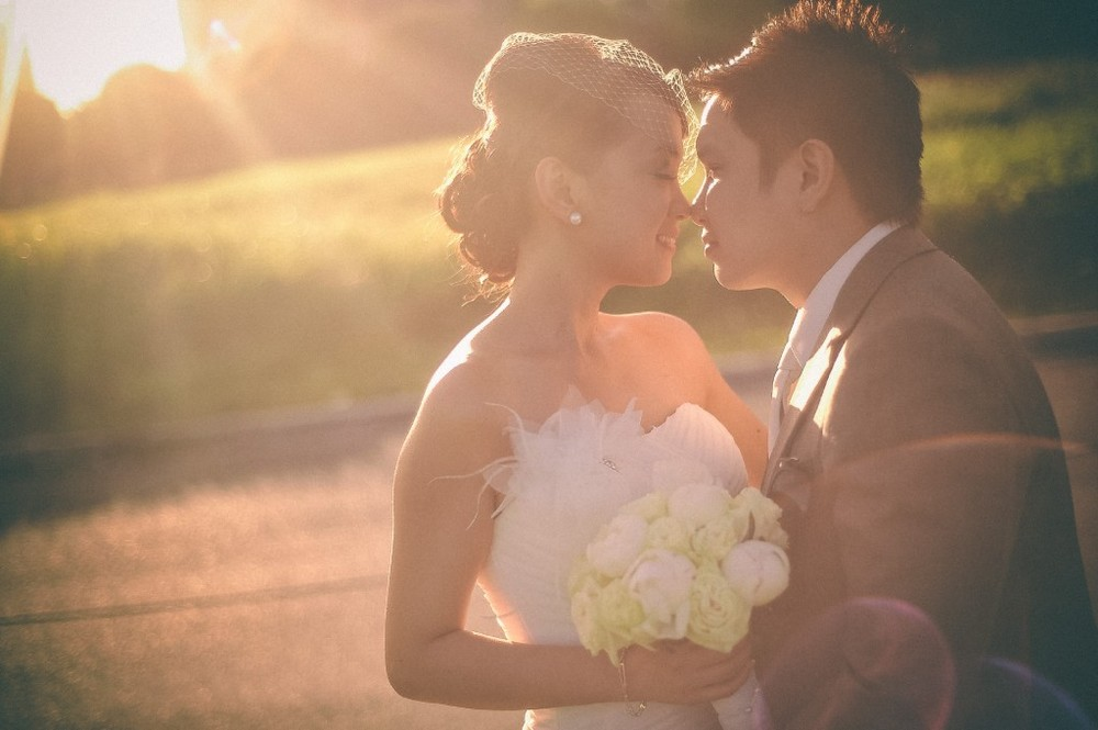 san   diego wedding photographer | bride and groom about to kiss with sunlight   radiating from upper left of image