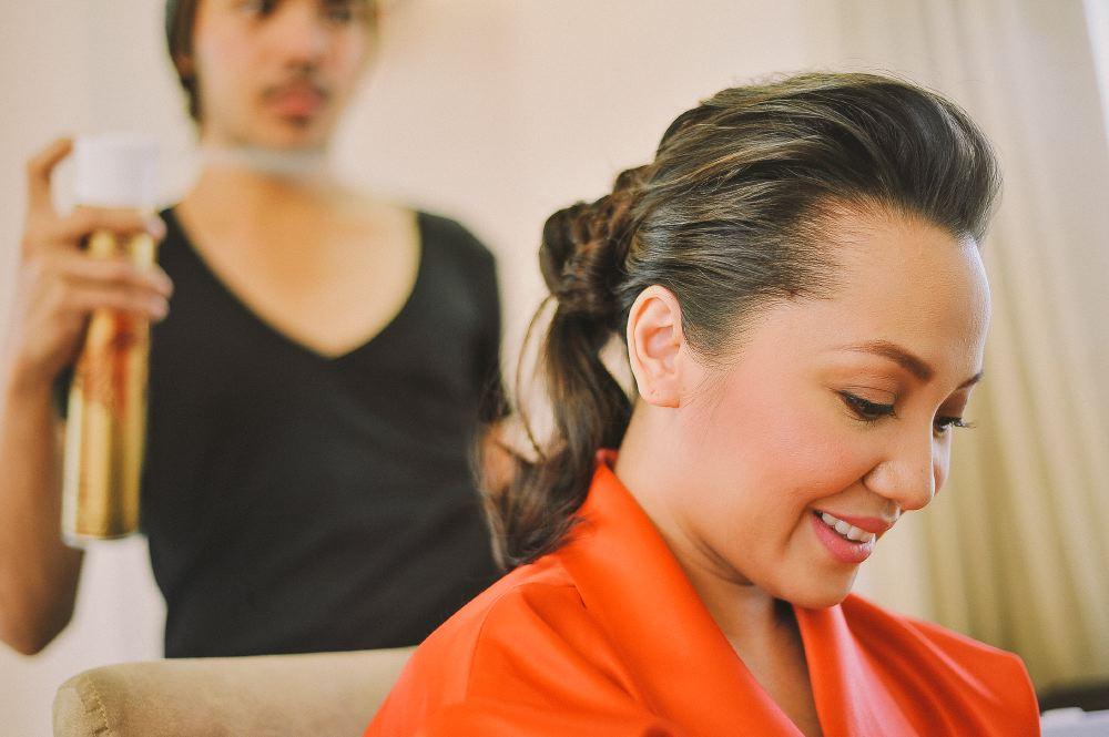 san   diego wedding photographer   woman sitting down with hair being sprayed