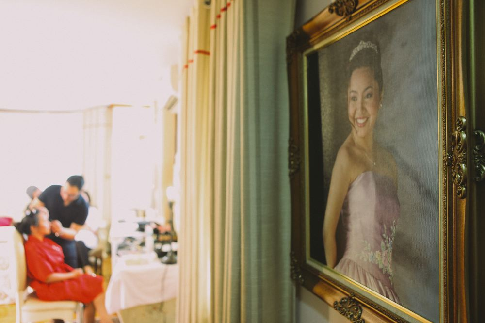 san   diego wedding photographer   closeup shot of painting of woman with woman in   red dress in background