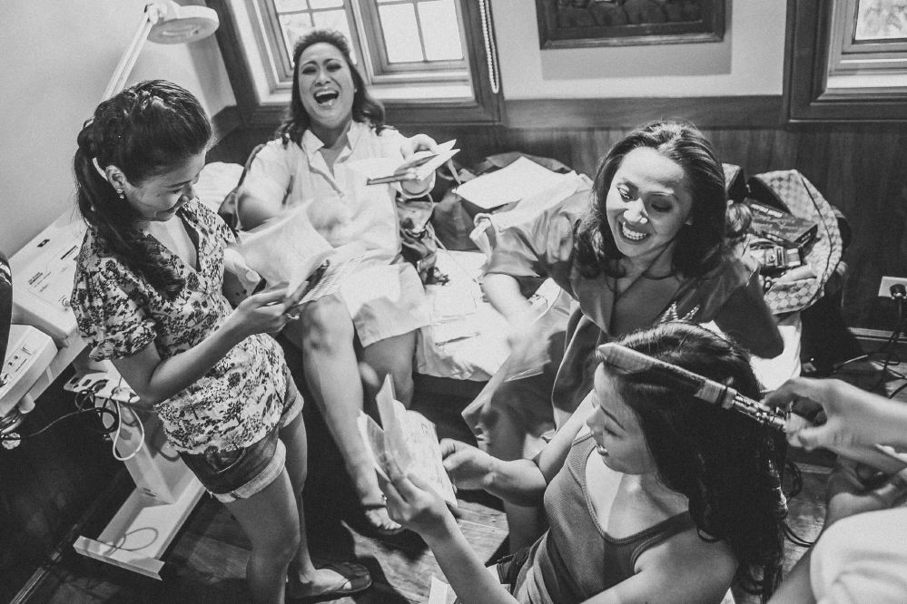 san   diego wedding photographer   monotone shot of women getting ready laughing   with messy items behind them