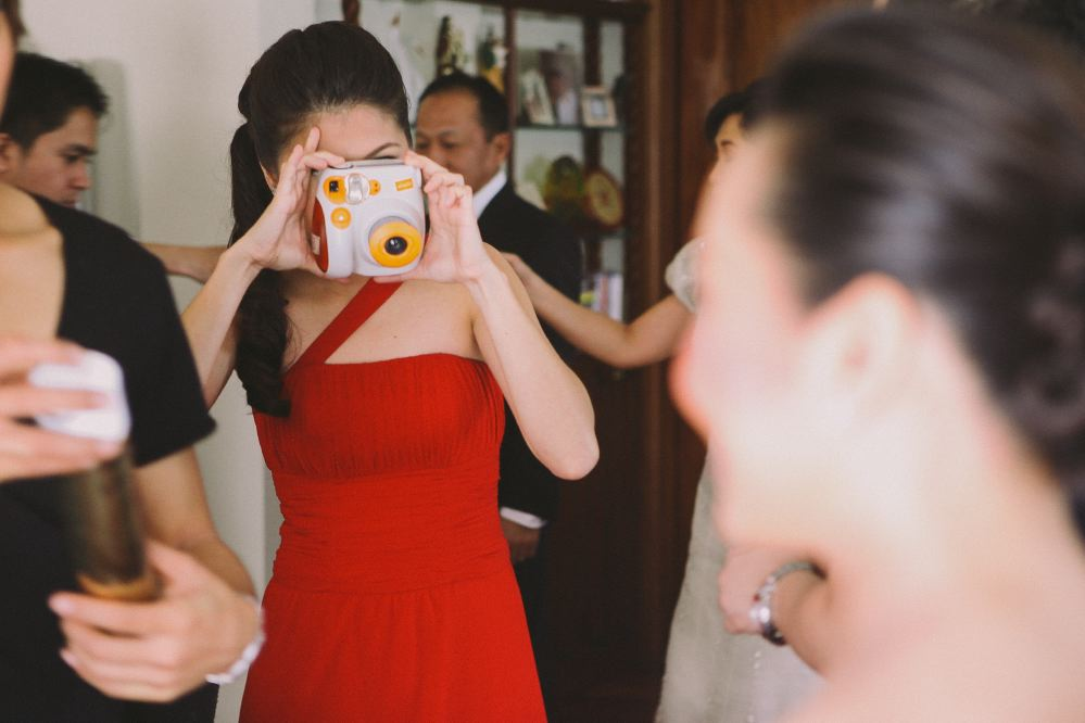 san   diego wedding photographer   woman in red dress taking picture with instax