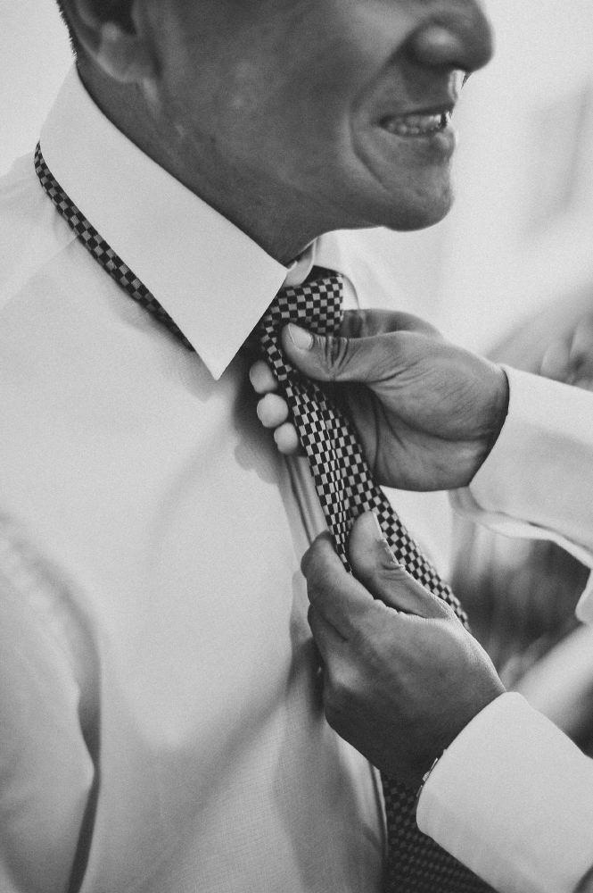 san   diego wedding photographer   monotone shot of man's tie being fixed