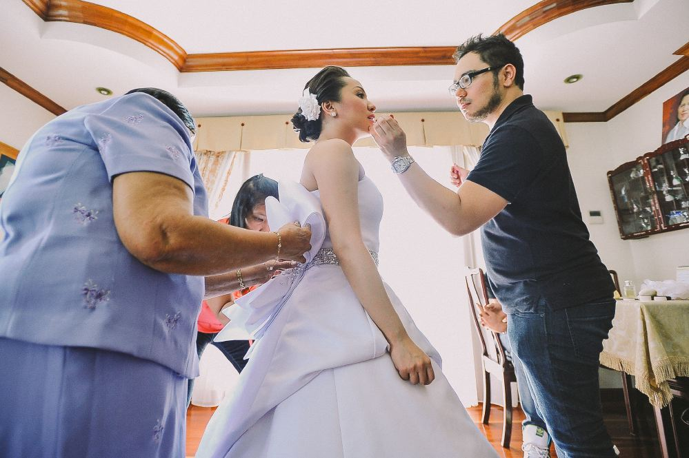 san   diego wedding photographer   woman in wedding dress being made up while   standing