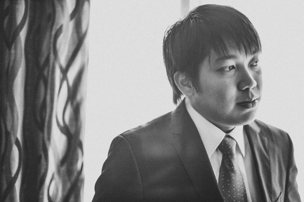 san   diego wedding photographer   monotone shot of man in suit with curtain behind   him
