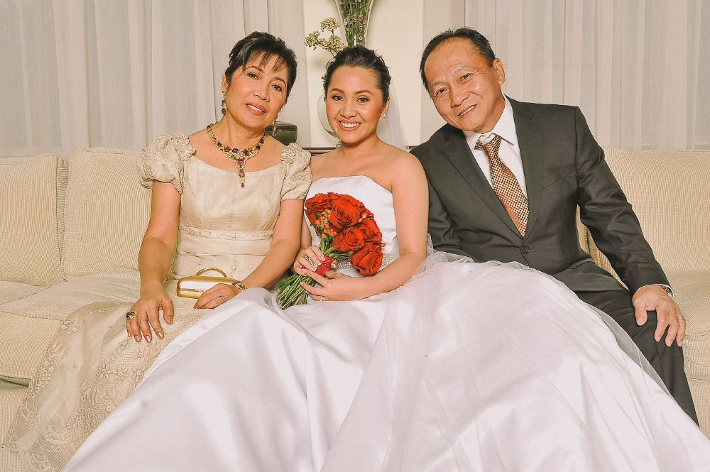 san   diego wedding photographer   bride sitting down with her parents holding red   bouquet