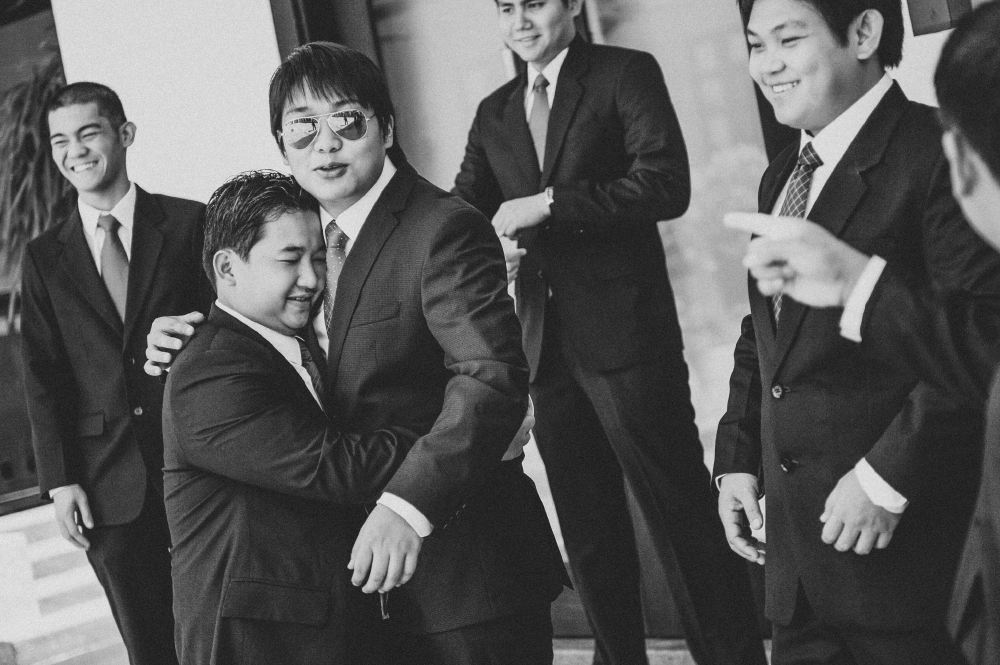 san   diego wedding photographer   monotone shot of groom and groomsmen with groom   being hugged