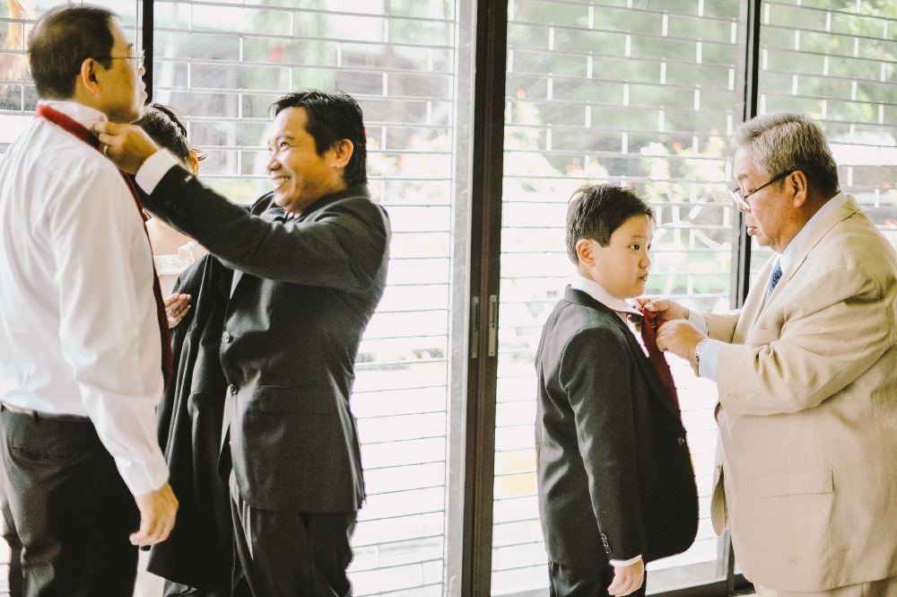 san   diego wedding photographer   men preparing their suits with window in   background