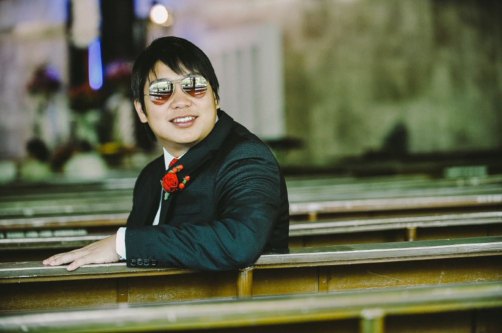 san   diego wedding photographer   man in suit and aviators sitting down on church   pew