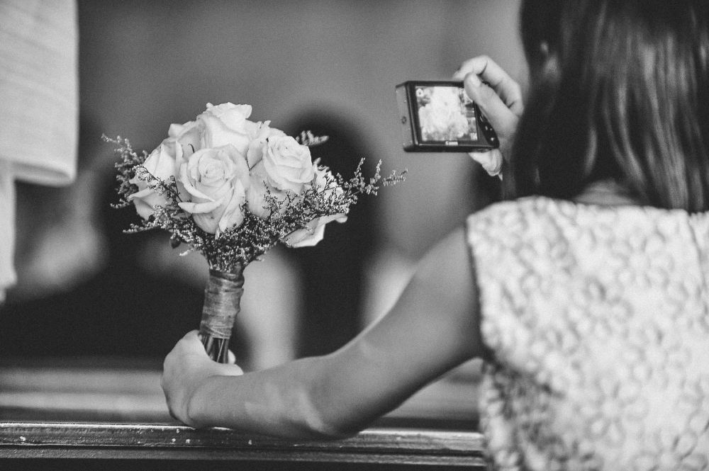 san   diego wedding photographer   monotone shot of woman taking picture of bouquet