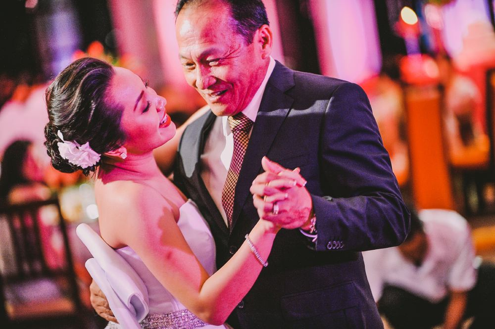 san   diego wedding photographer   bride dancing with her father illuminated by red   and pink lights