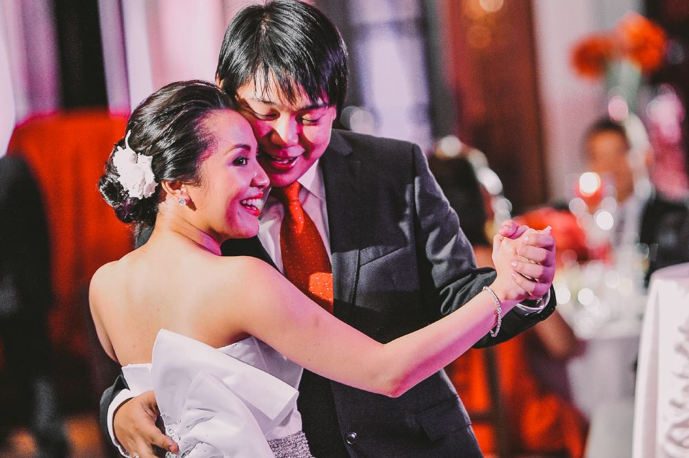 san   diego wedding photographer   bride dancing with groom illuminated with violet   and pink lights