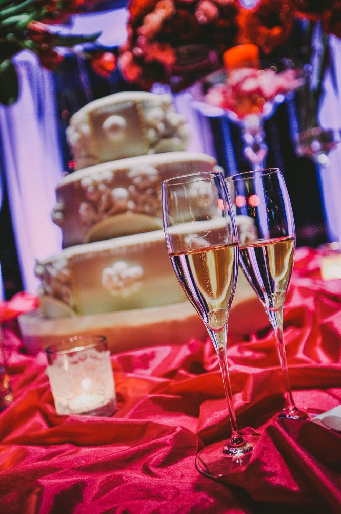san   diego wedding photographer   closeup shot of champagne glasses with wedding   cake in background