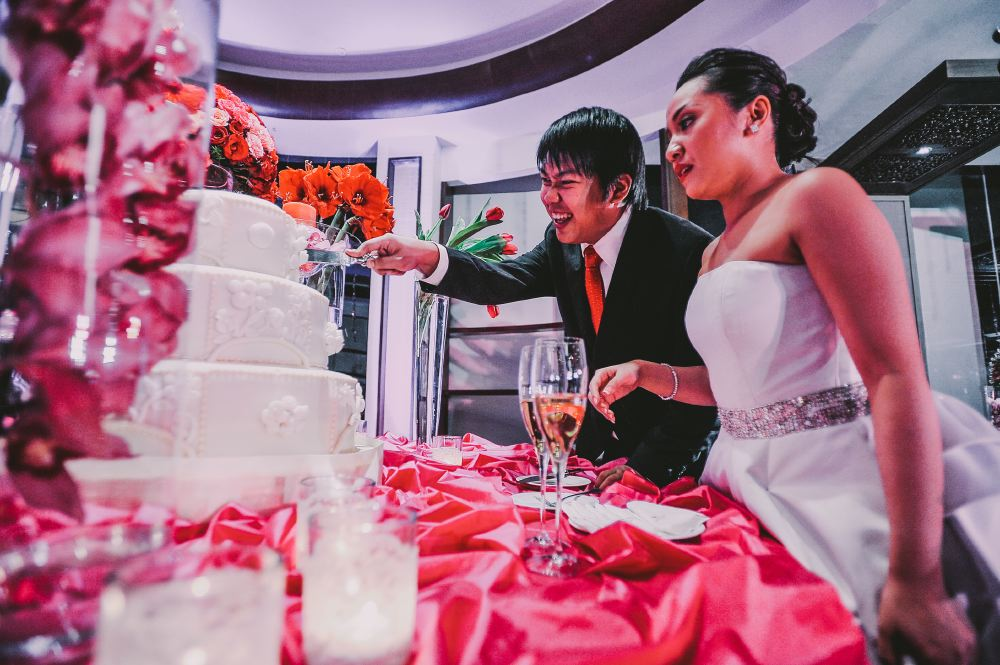 san   diego wedding photographer   newly married couple slicing cake with groom   smiling