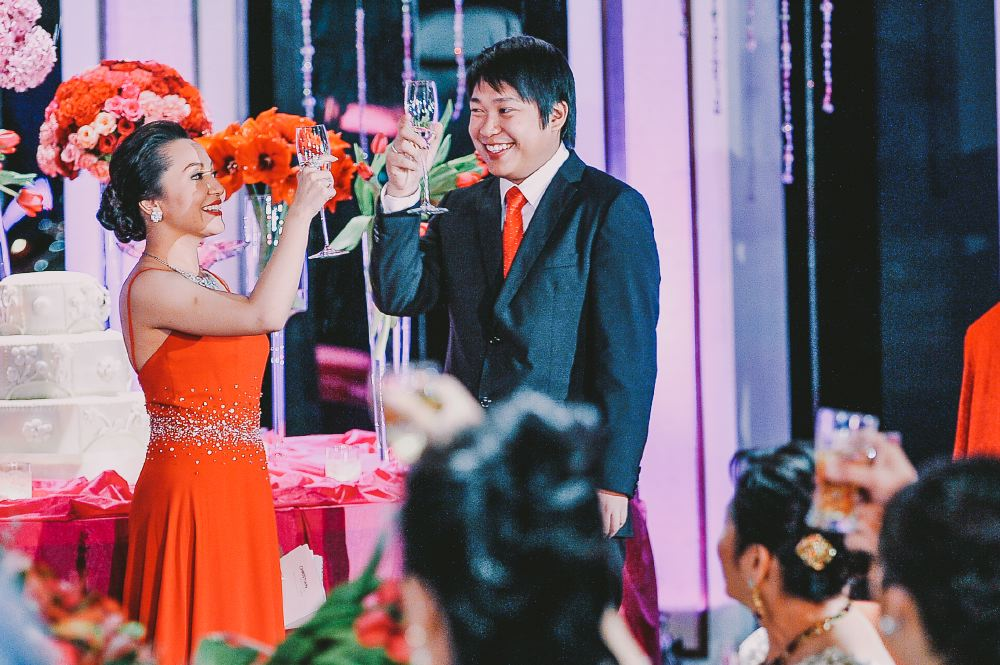 san   diego wedding photographer   groom holding up glass of champagne with woman   in red dress