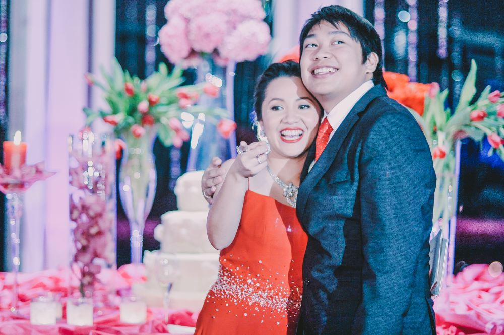 san   diego wedding photographer   groom holding bride in red dress close in front   of wedding cake