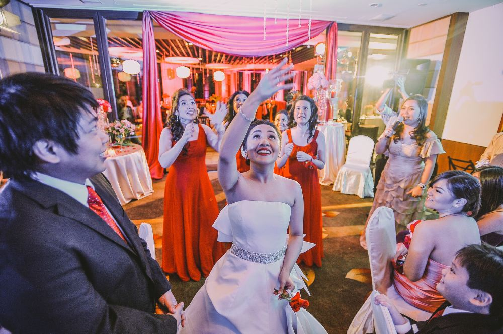 san   diego wedding photographer   bride throwing red roses with women in red   dresses waiting behind her