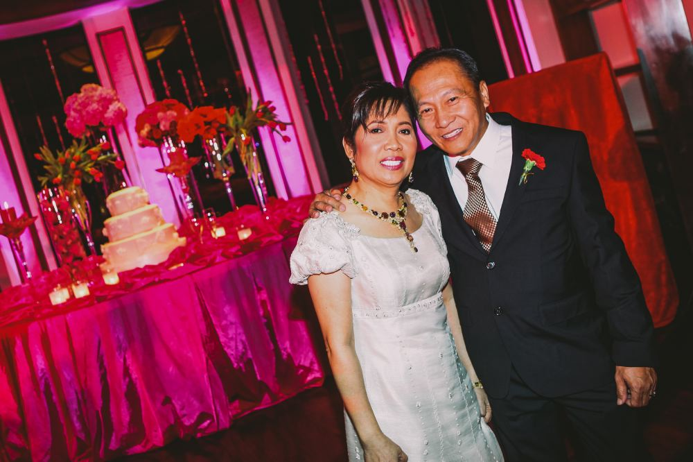 san   diego wedding photographer   shot of middle aged couple posing in front of   wedding cake