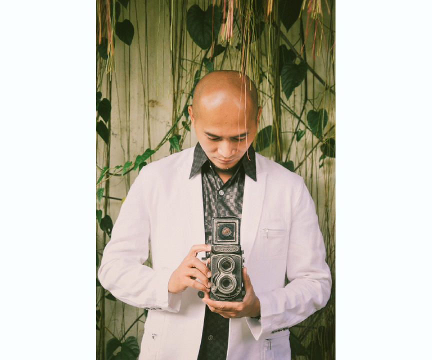 san   diego wedding photographer | man with old camera standing in front of wall   with vines