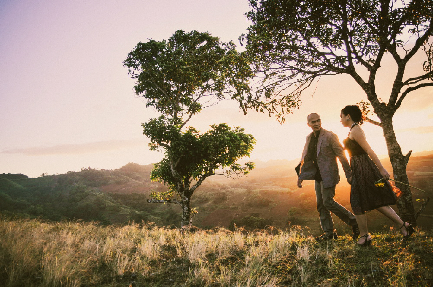 san   diego wedding photographer | man and woman walking with sun about to set and   2 trees behind them