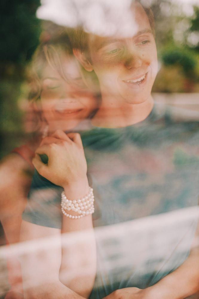 san   diego wedding photographer | woman hugging man from behind glass window   reflecting trees