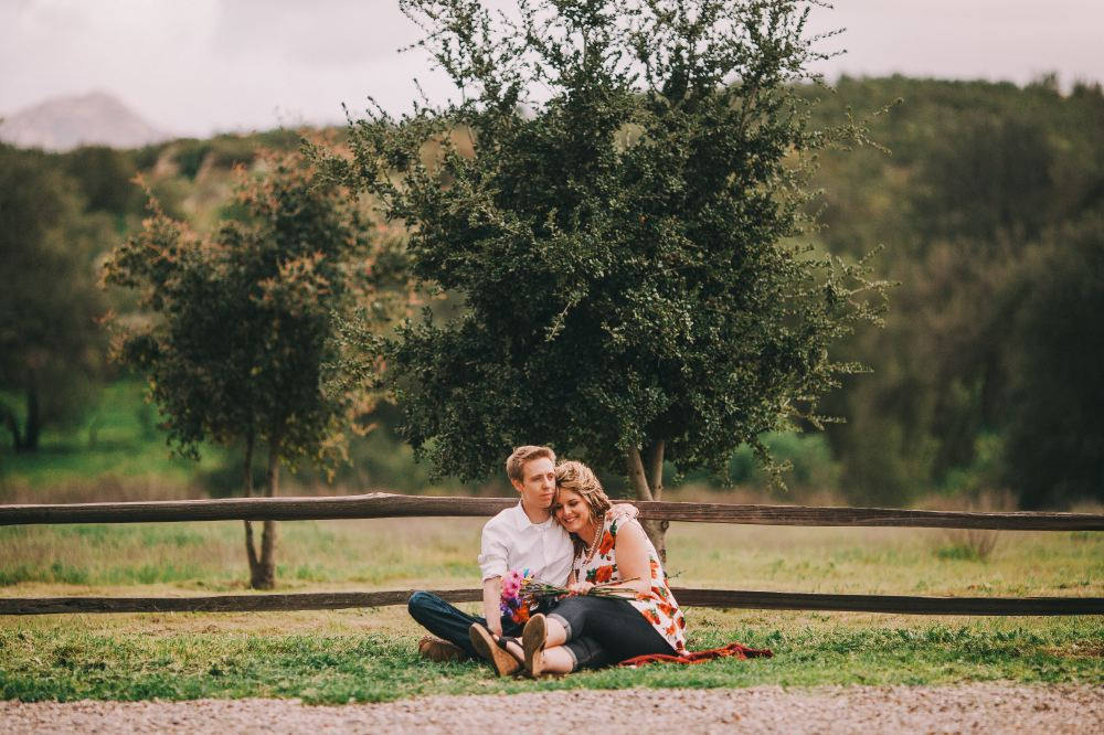 san   diego wedding photographer | man and woman sitting together in front of   wooden fence