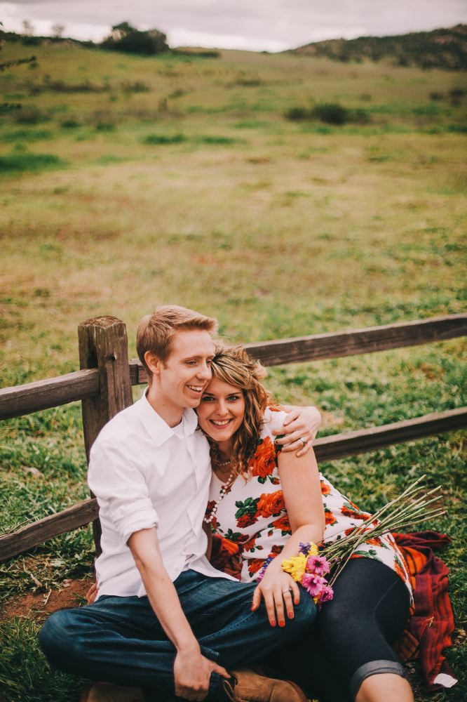 san   diego wedding photographer | man holding woman in floral dress and pearls   sitting down