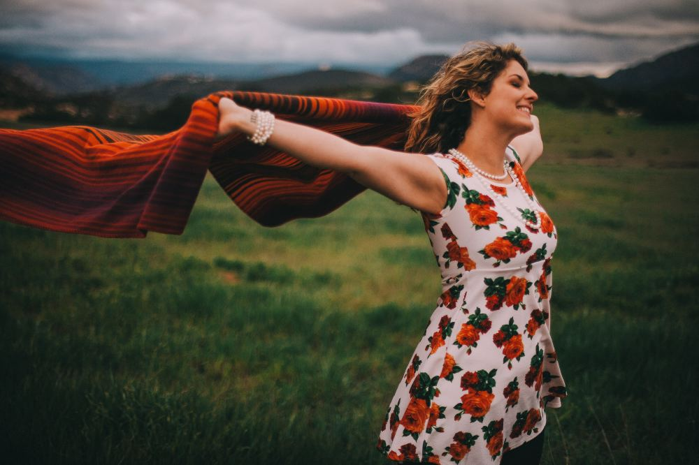 san   diego wedding photographer | woman with arms up raising blanket behind her