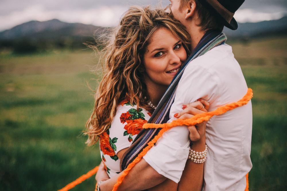 san   diego wedding photographer | woman hugging man wrapped around in orange yarn