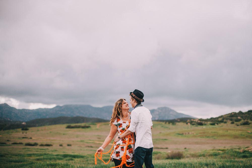 san   diego wedding photographer | woman wrapped around orange yarn smiling at man   in hat