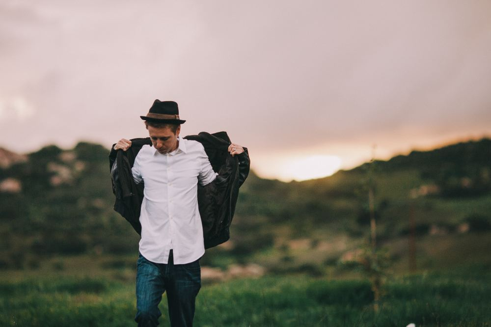 san   diego wedding photographer | man about to put on jacket with sunset in   background