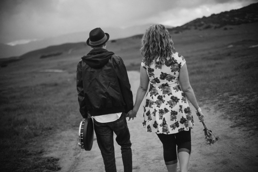 san   diego wedding photographer | man in leather jacket holding banjo walking hand   in hand with woman
