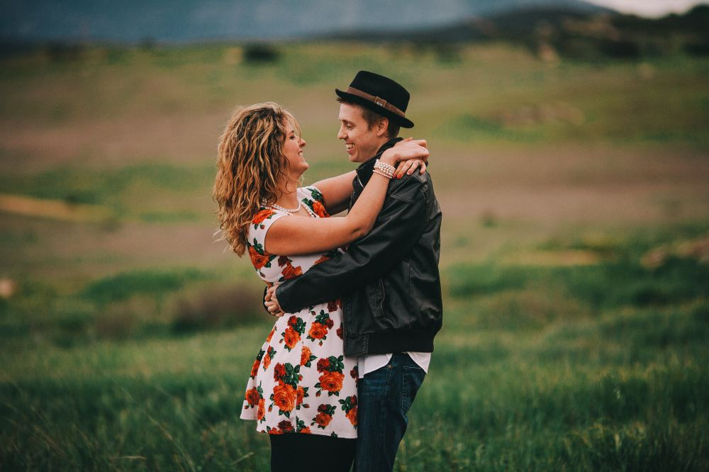 san   diego wedding photographer | man in leather jacket and hat holding woman in   floral dress