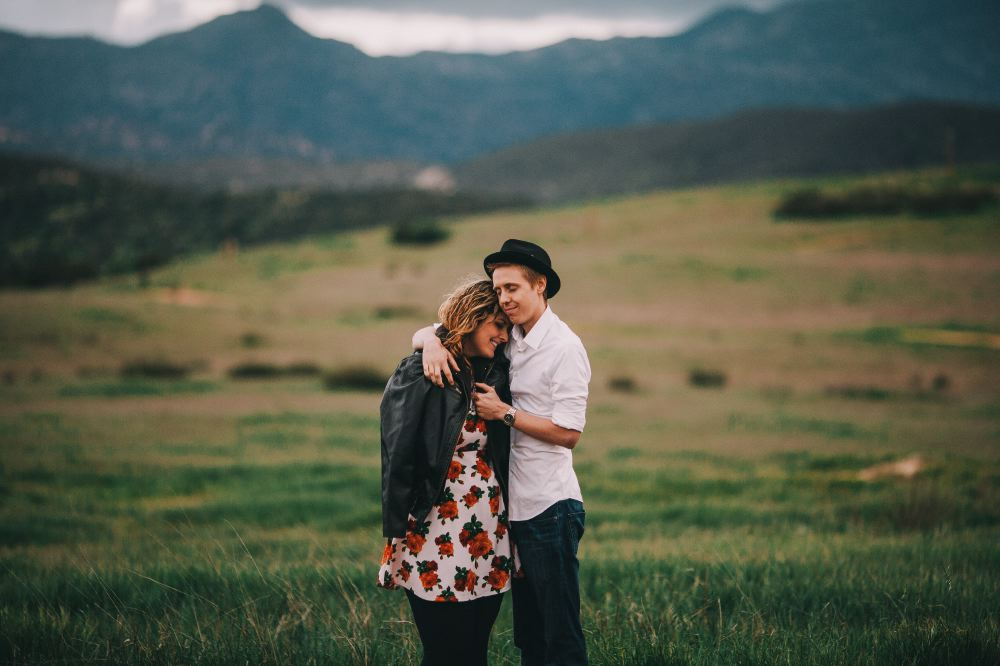 san   diego wedding photographer | man hugging woman in floral dress and leather   jacket