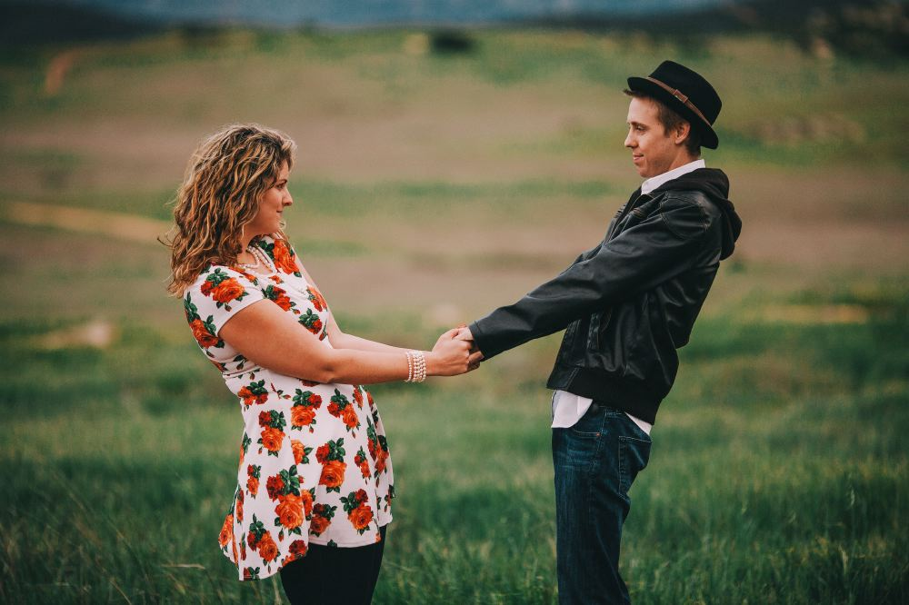 san   diego wedding photographer | man in leather jacket holding extended hands   with woman in floral dress