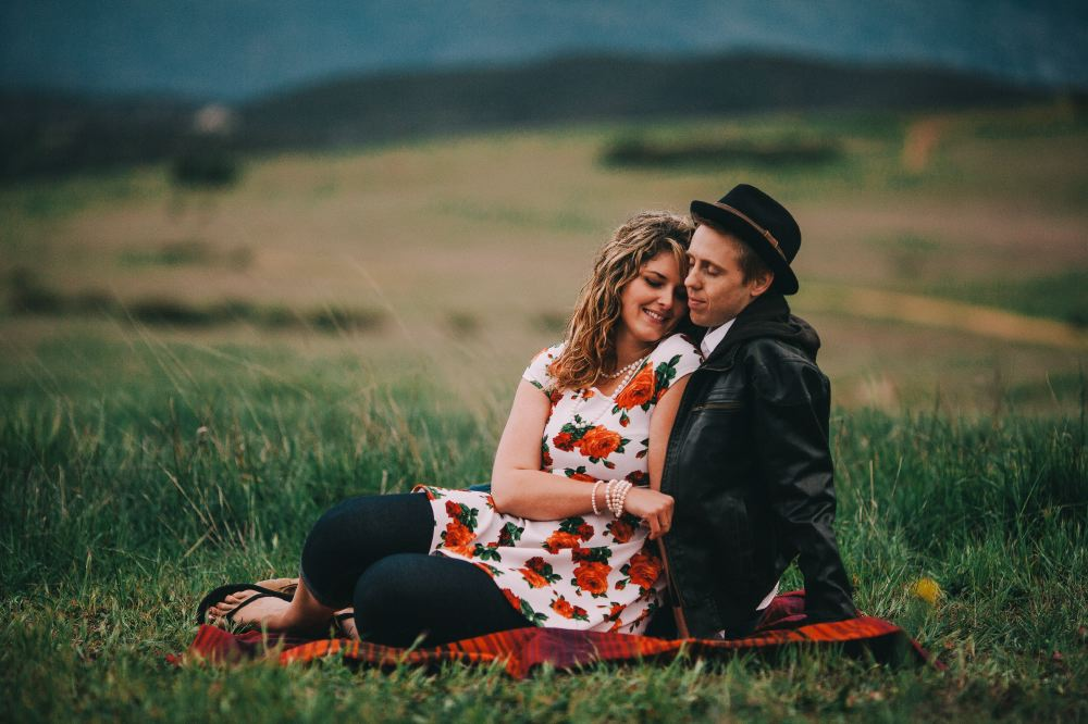 san   diego wedding photographer | woman leaning against man in leather jacket and   cap on blanket