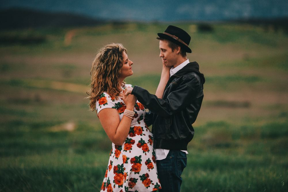 san   diego wedding photographer | woman holding man in leather jacket and hat's   face