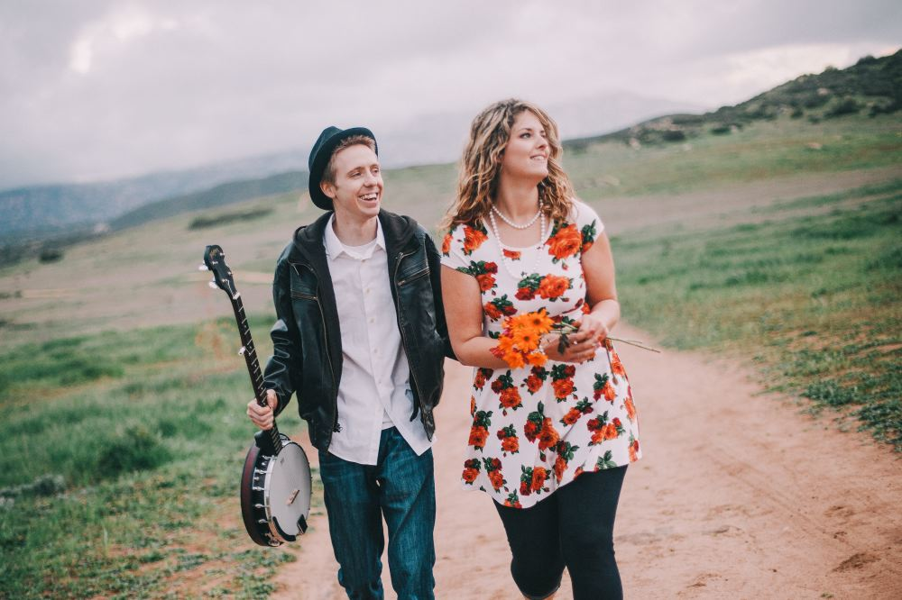 san   diego wedding photographer | woman with bunch of orange flowers walking with   man in leather jacket