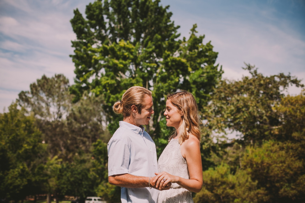 san   diego wedding photographer | blonde man in ponytail and blonde woman facing   each other holding hands and smiling