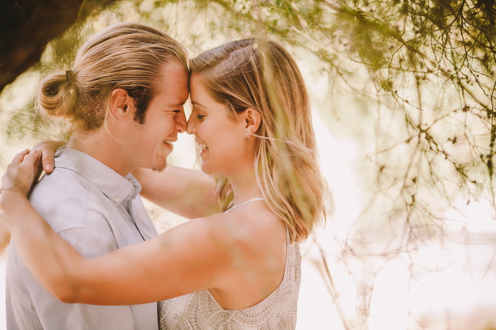 san   diego wedding photographer | blonde woman with arms hugging shoulders of   blonde man in ponytail while facing each other and with noses together