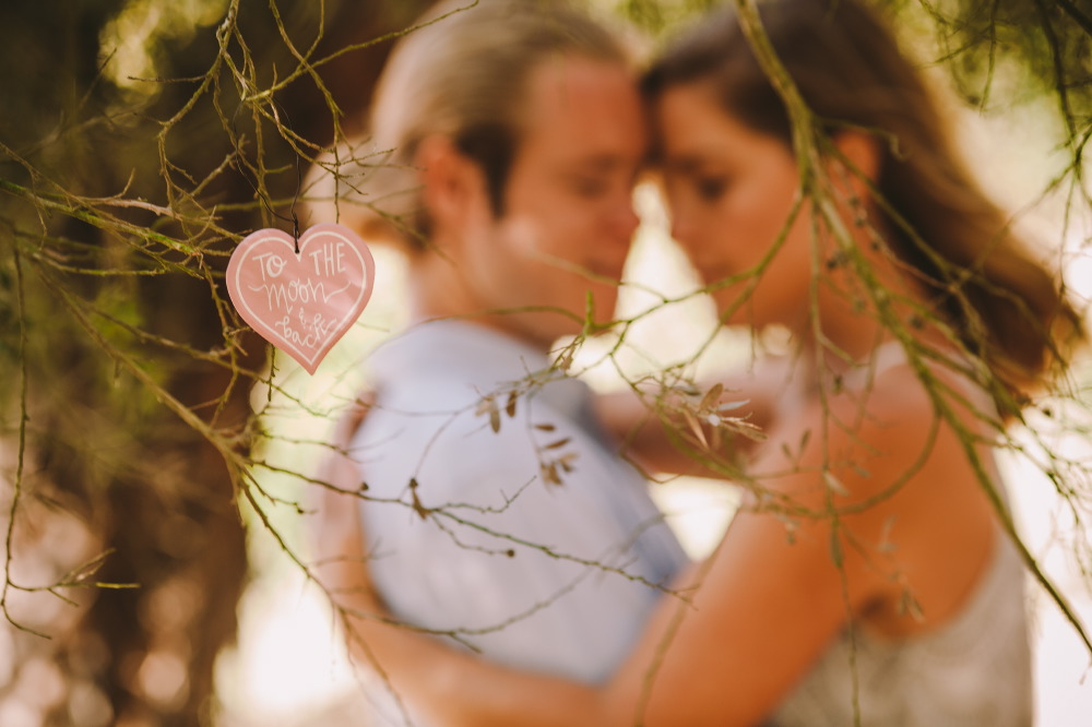 san   diego wedding photographer | heart-shaped note hanging on tree with blonde   couple hugging in background