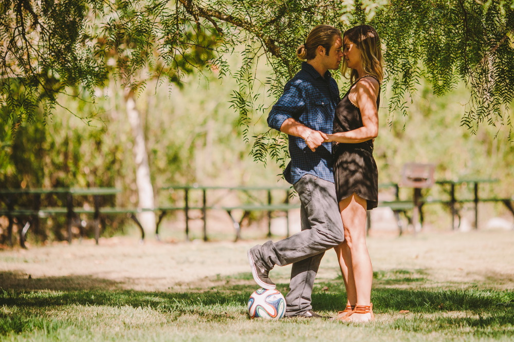 san   diego wedding photographer | blonde man in ponytail and dark blue polo   stepping on soccer ball and holding hands of blonde woman
