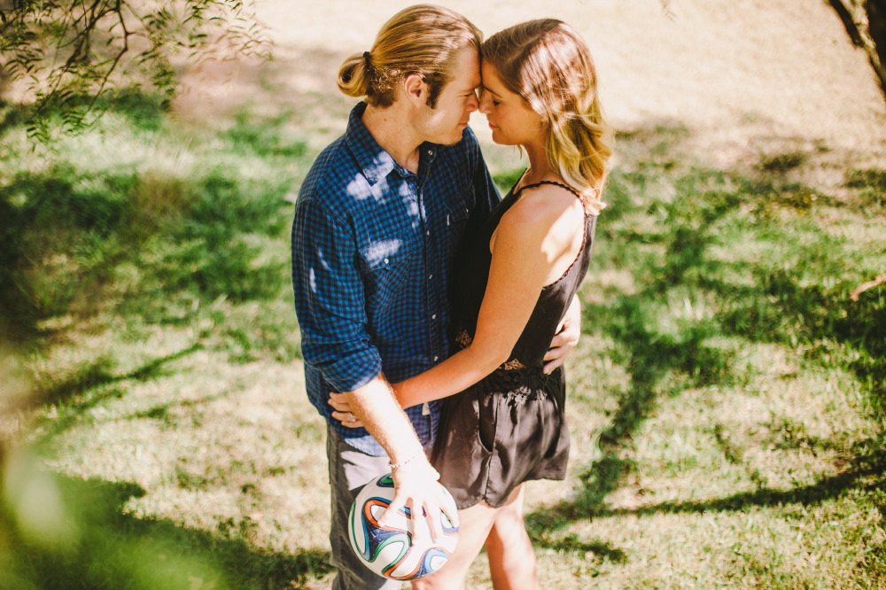 san   diego wedding photographer | blonde man in ponytail and dark blue polo   holding soccer ball and hugging waist of blonde woman